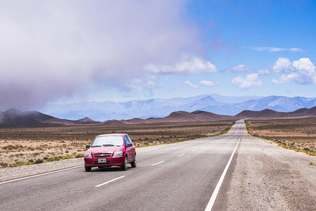 Car Driving Down Empty Desert Highway