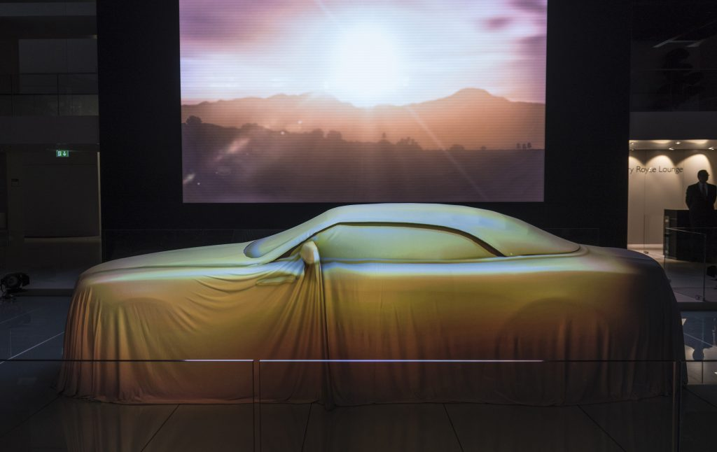 The Rolls-Royce Dawn convertible under a sheet at its debut