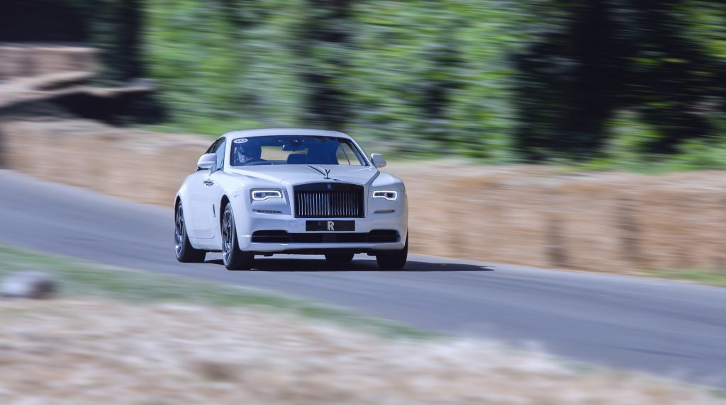A white Rolls-Royce Wraith coupe driving down a tree-lined road