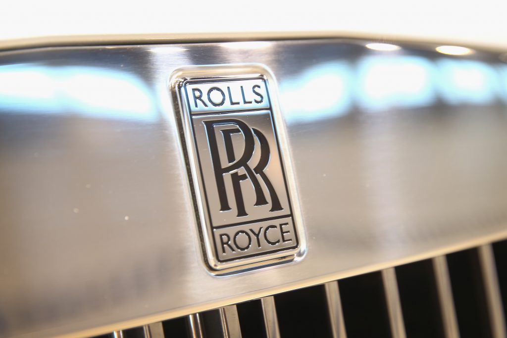 The Rolls-Royce emblem stamped into a chrome badge on a chrome grille