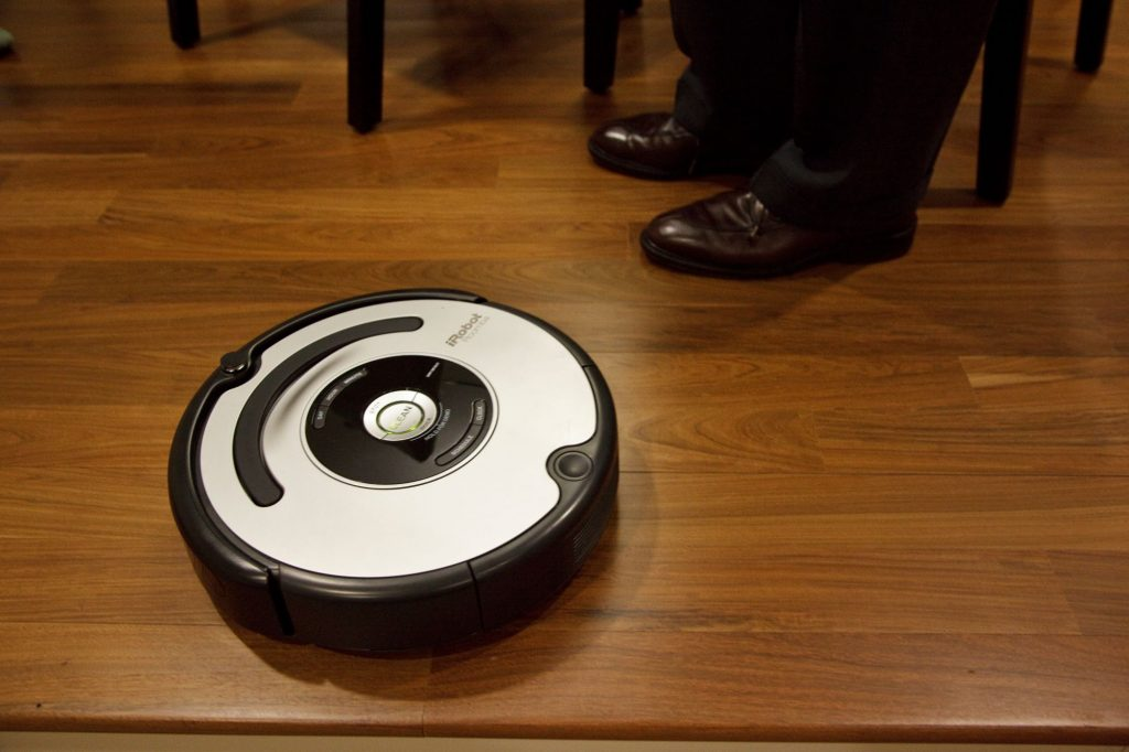 A Roomba autonomous vacuum cleaner on a wooden floor