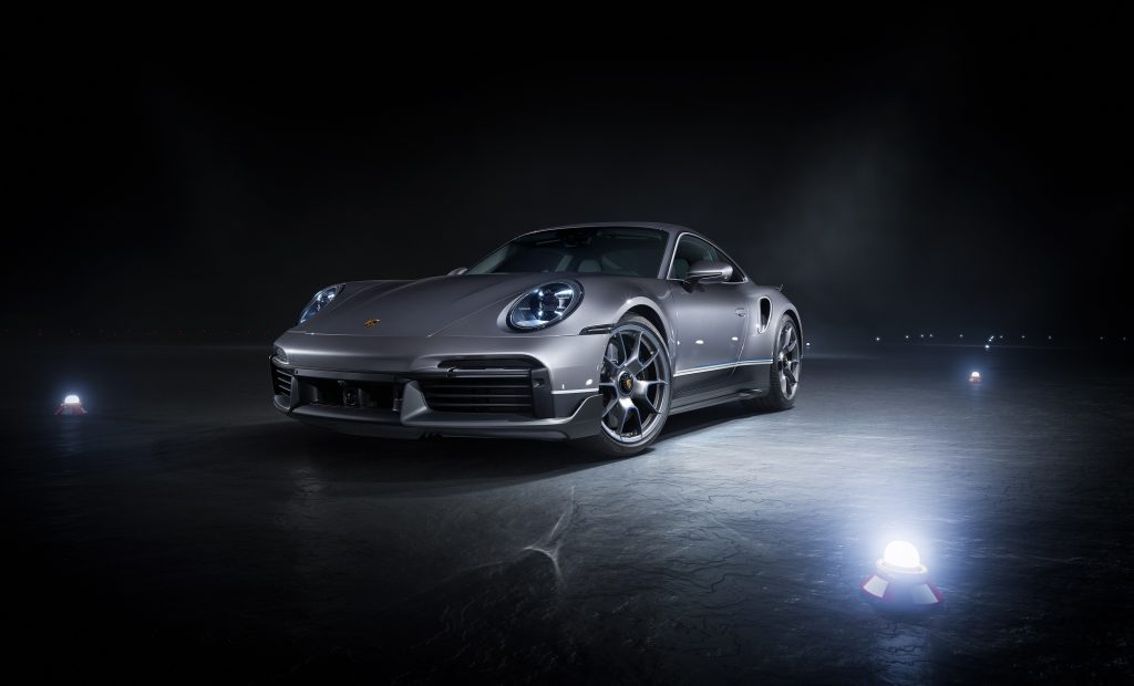 A silver Porsche 911 Turbo S surrounded by lights at a photoshoot