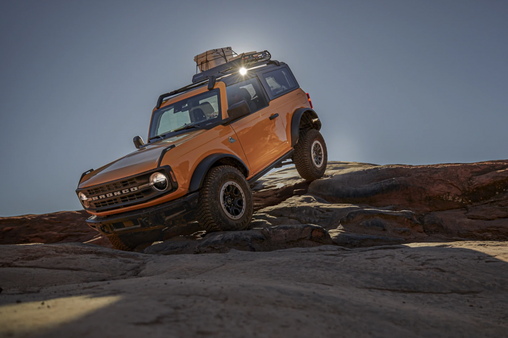 A yellow 2021 Ford Bronco off-roading over rocks