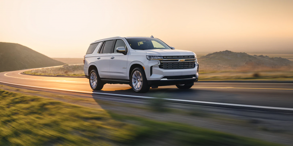 A white 2021 Chevy Tahoe driving at dusk