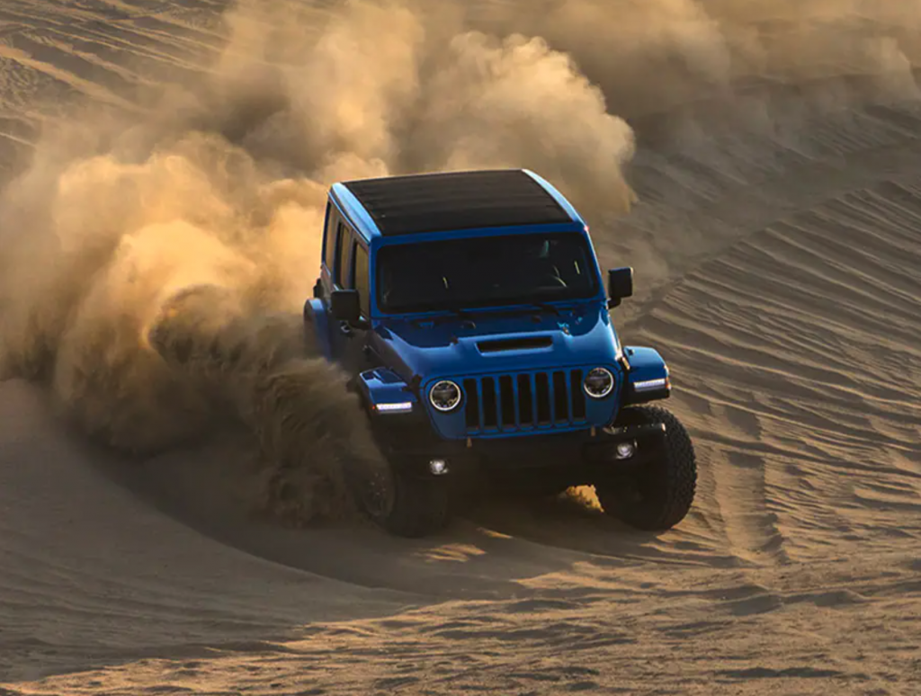 A blue 2021 Jeep Wrangler Rubicon 392 off-roading in sand
