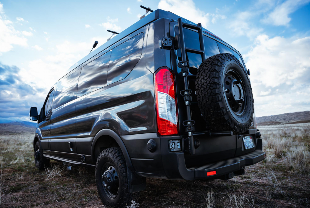 The exterior of a black ModVans CV1 with beefy off-road tires and a suspension lift