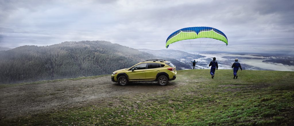 Subaru Crosstrek parked on a cliff as a hang glider takes off