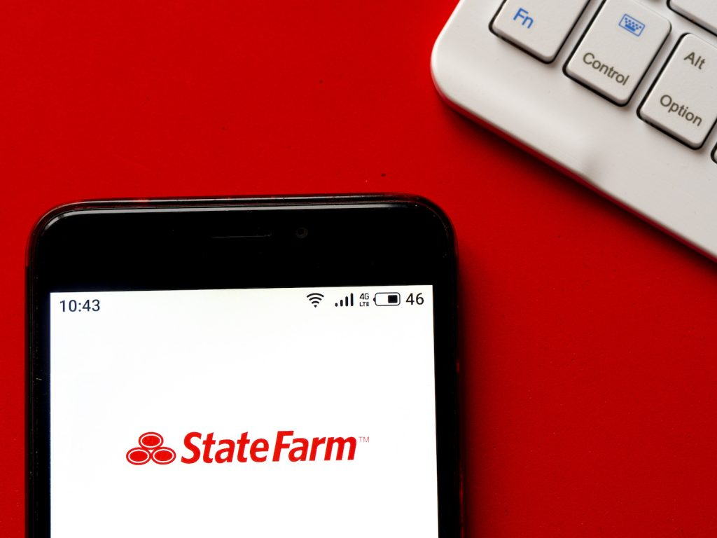An iPhone sitting on top of a desk with the StateFarm logo shown on the screen, StateFarm is one of the cheapest car insurance companies