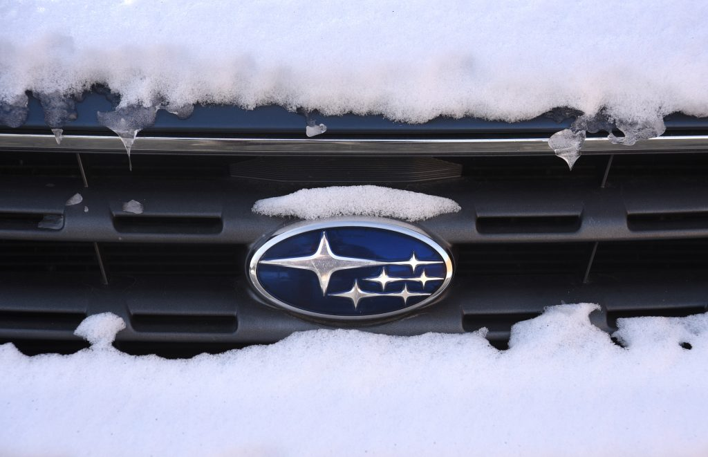 A snow-covered Subaru logo badge on the front grille of a car