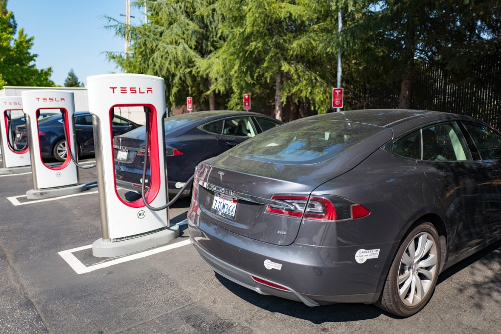 Tesla vehicles are plugged in and charging at a Supercharger rapid battery charging station