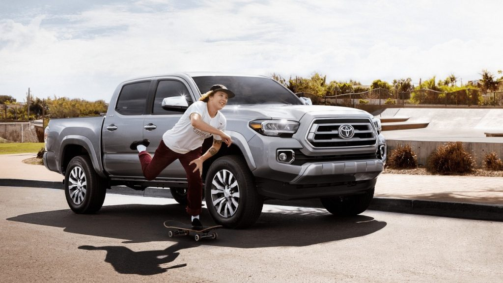 A silver 2021 Toyota Tacoma sits parked at a curb as a person skateboards by.