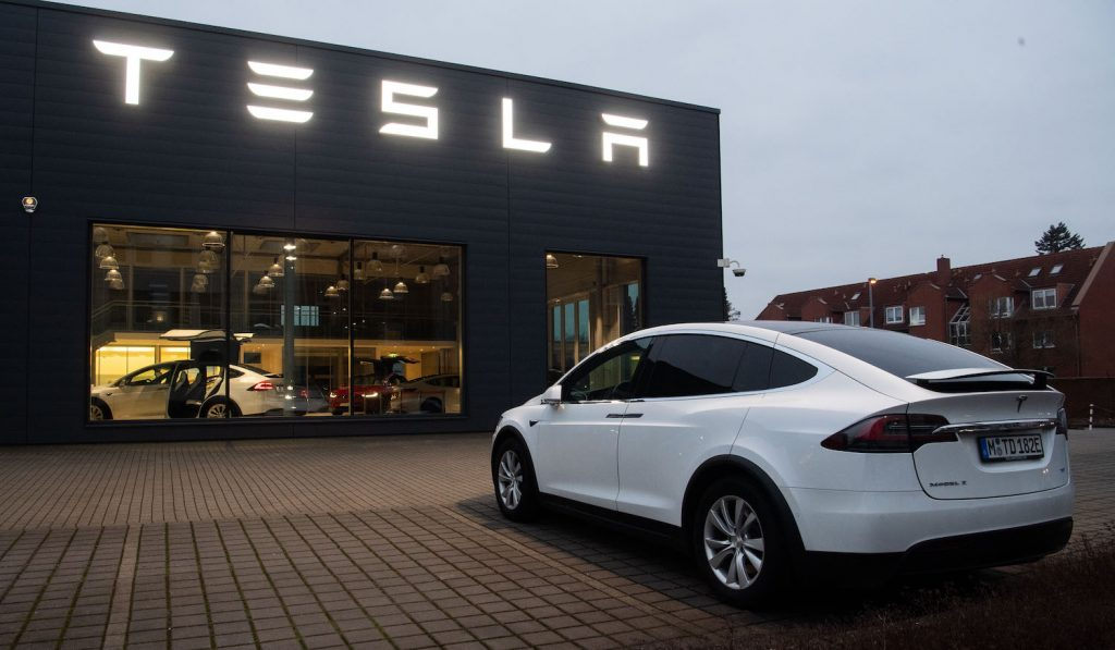 A white 2020 Tesla Model X in front of a Tesla store