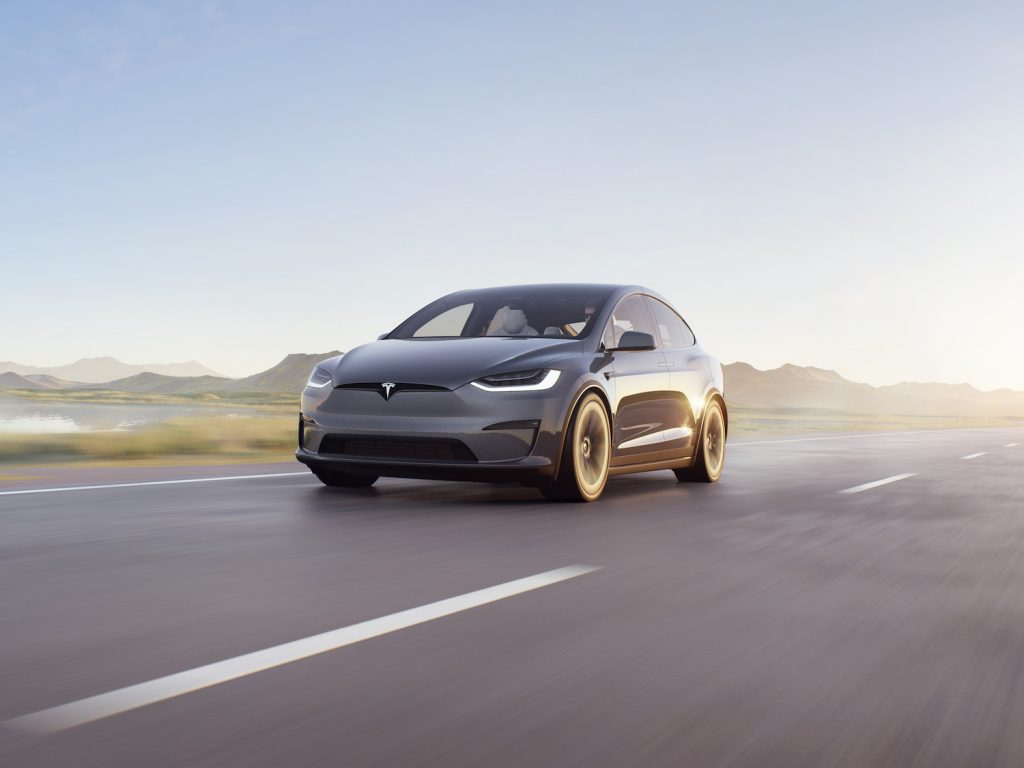 A dark Tesla Model X driving down an empty road with the sun shining behind it, the Tesla Model X is a Tesla SUV and is the first Tesla car 'Ted Lasso' star Jason Sudeikis has ever owned