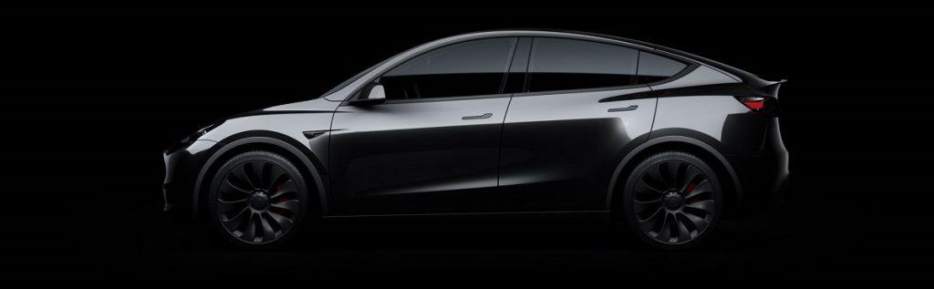 A dark gray Tesla Model Y against a black background.