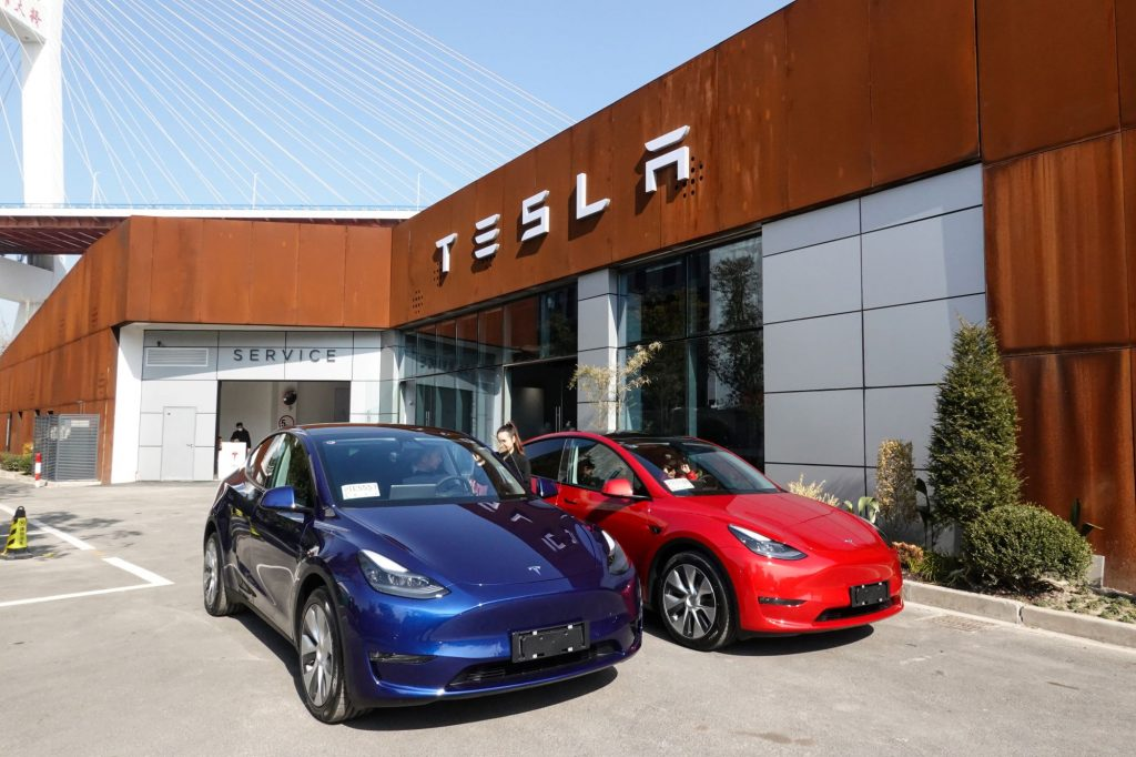 A pair of blue and red Tesla models parked outside of a Tesla showroom building