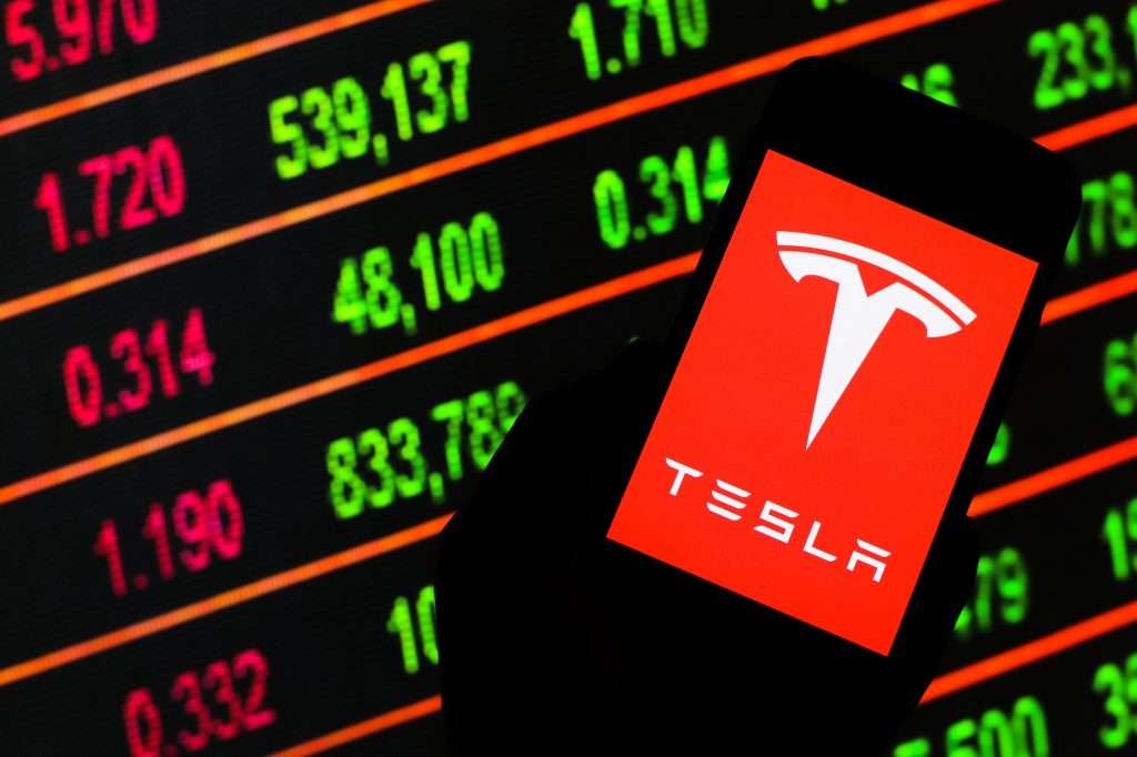 A Tesla logo displayed on a smartphone in front of lighted stock ticker board
