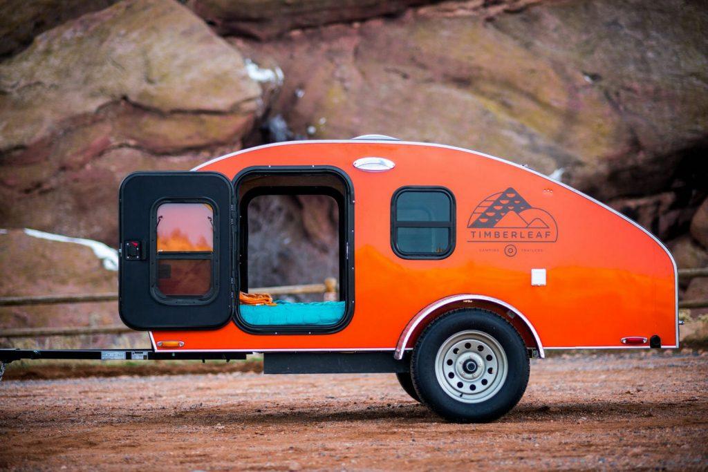 An orange Timberleaf Classic Teardrop Trailer parked, the Timberleaf Classic Teardrop Trailer is one of the coolest teardrop campers