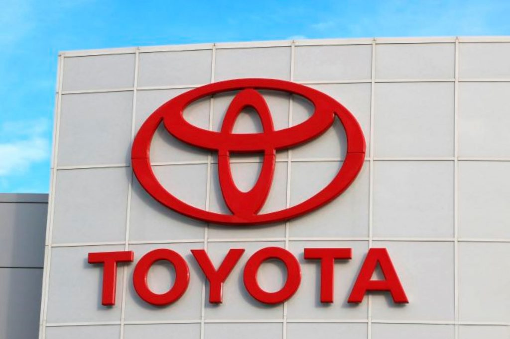 Closeup of Toyota's logo in red on the front of a ivory building with 'Toyota' written underneath it.