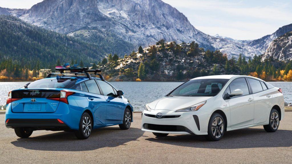 A blue Toyota Prius and a white Toyota Prius.