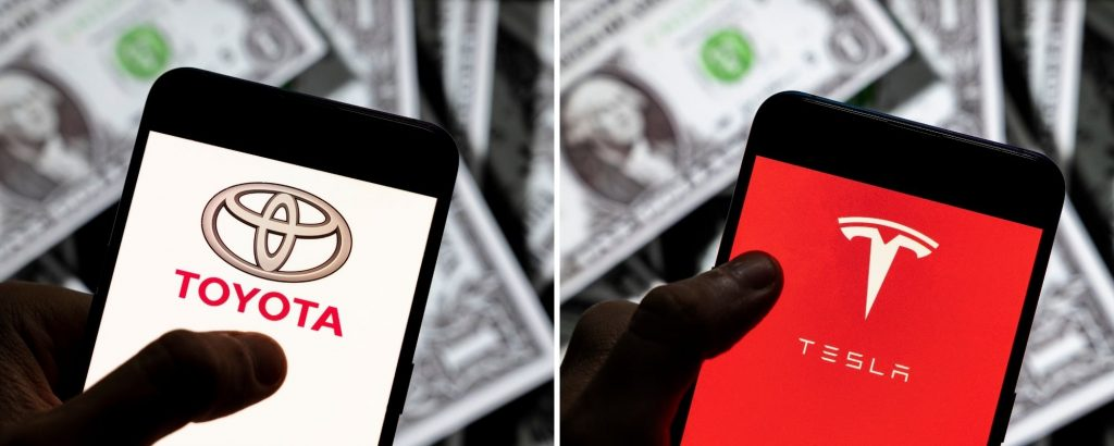 The Toyota and Tesla logos on smartphones with a background of dollar bills