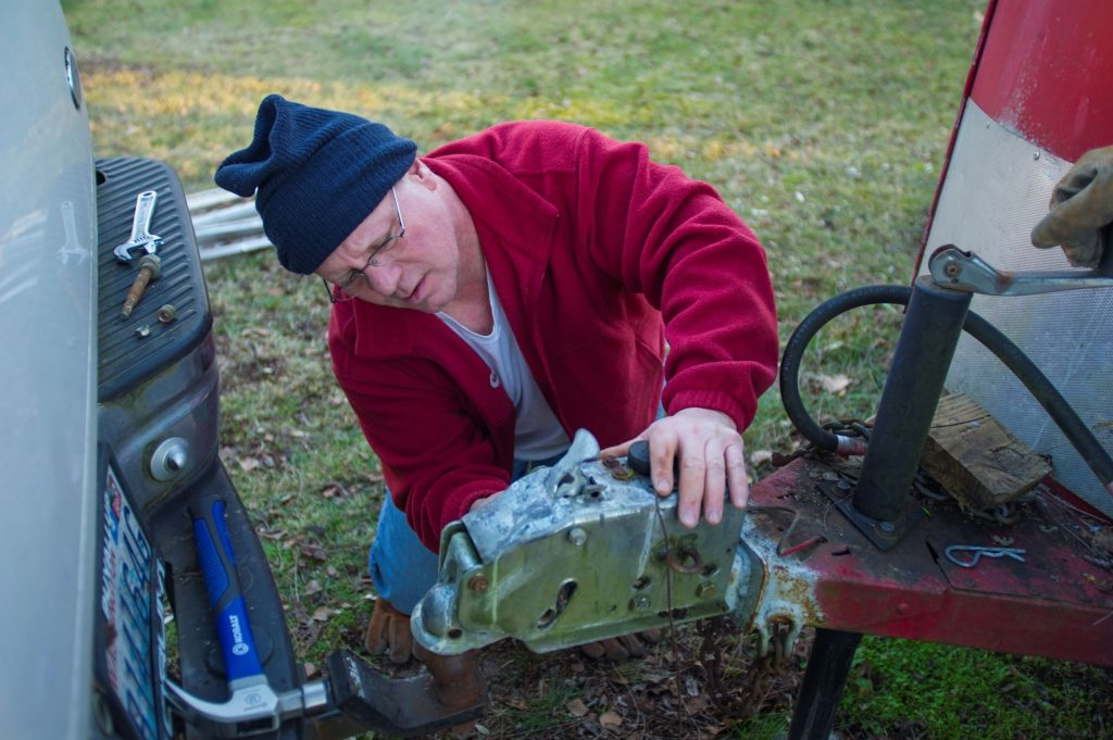 A man fixing a tow hitch to a horse trailer