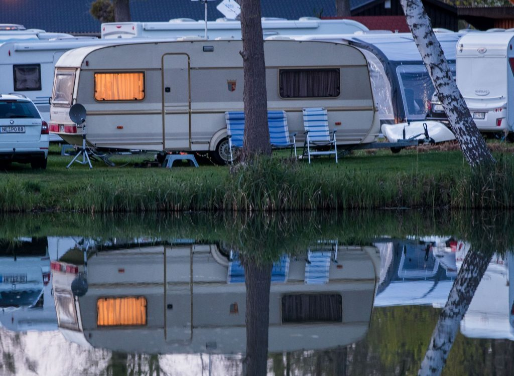 A cream and gray travel trailer with a single tree in the middle front, parked beyond a pond where the reflection of the RV can be seen. There are two darker blue and one lighter blue lawn chair in front of the travel trailer. There are other cars and travel trailers in the background.