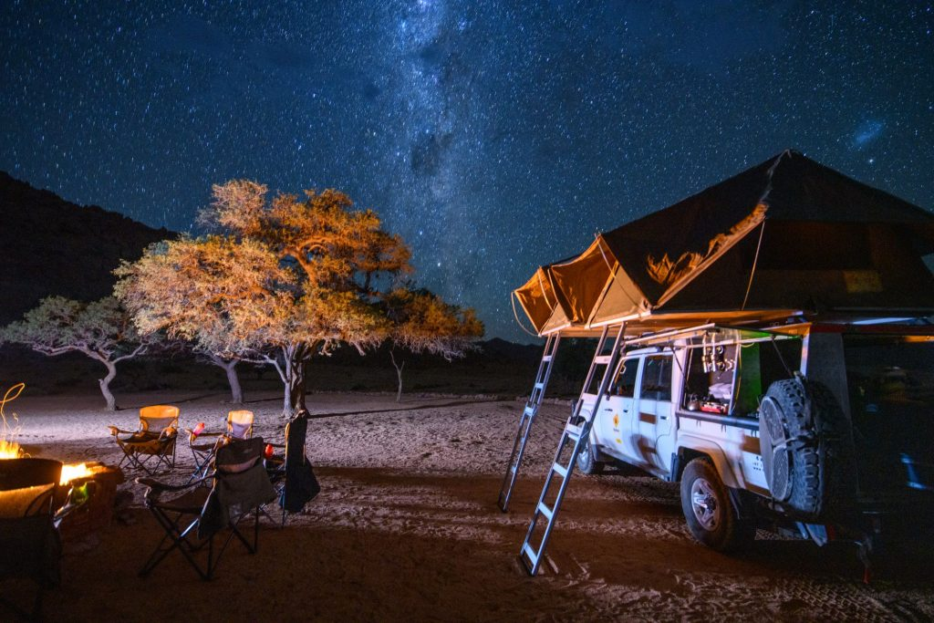 A truck bed tent set up near a campsite with a fire and a starry night sky