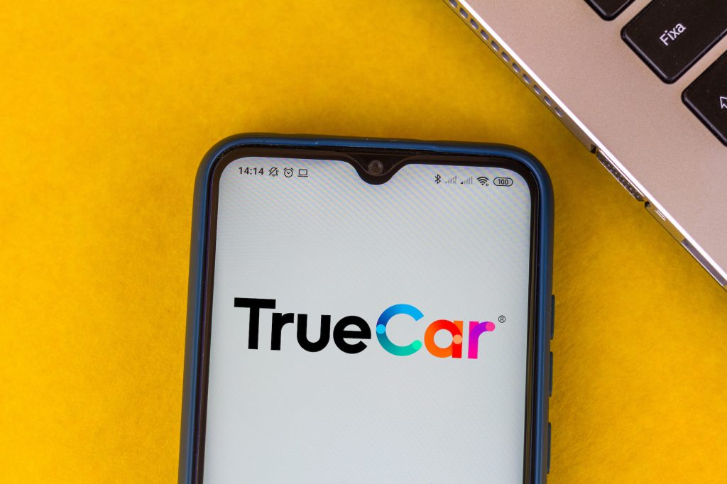 A photo illustration of the TrueCar logo displayed on a smartphone