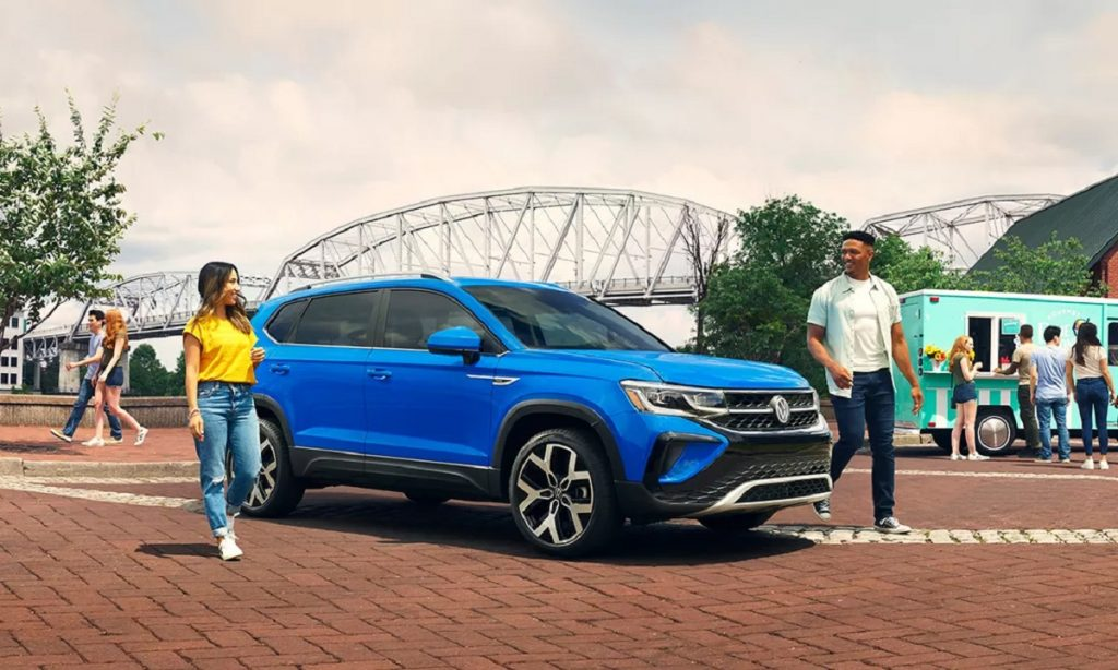 A bright blue 2022 Volkswagen Taos parked in front of a bridge.
