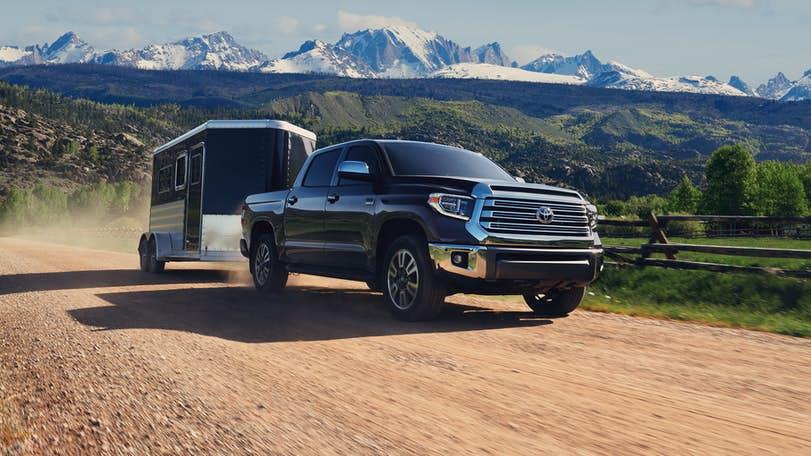 A black 2021 Toyota Tundra hauling a small trailer.