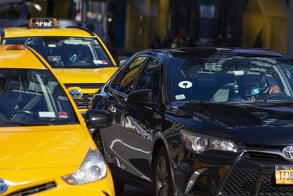 Yellow cabs and an Uber car drive through Times Square on November 16, 2020, in New York City