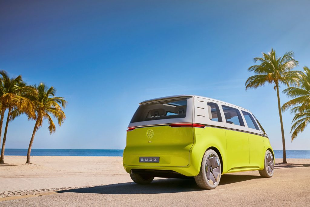 The Volkswagen ID. Buzz Concept in yellow and white parked on a tropical beach near palm trees