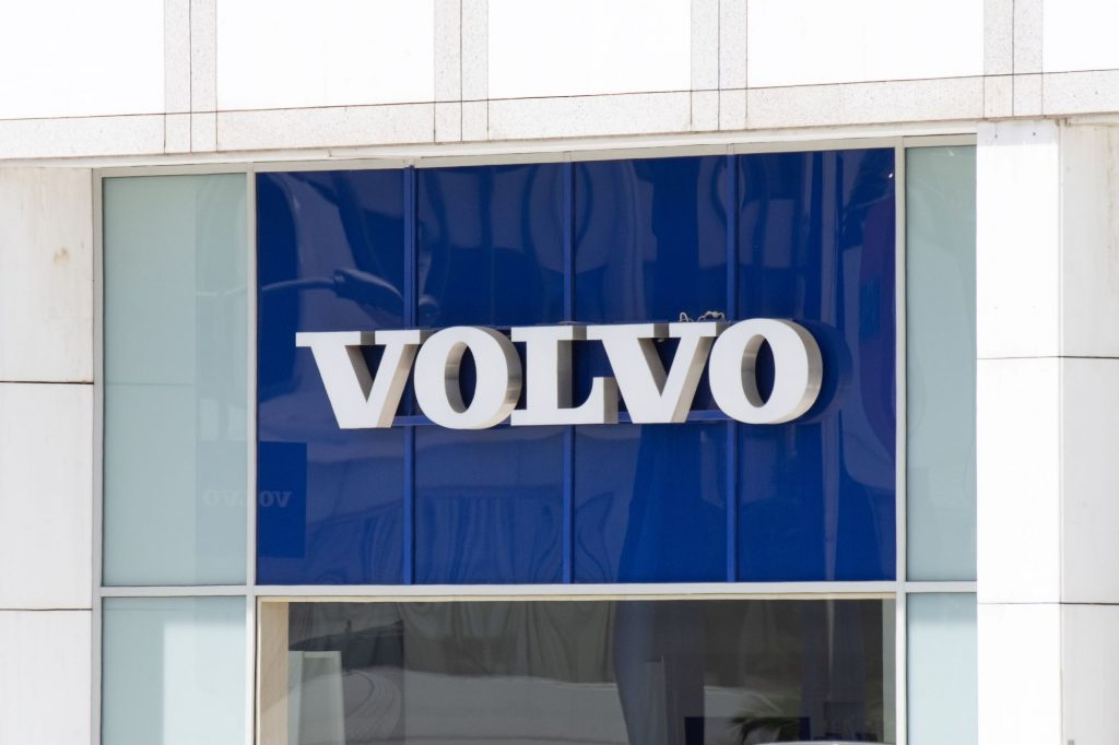 A large blue sign with 'Volvo' printed framed by a white section of what looks like a building with a glass window underneath the sign.