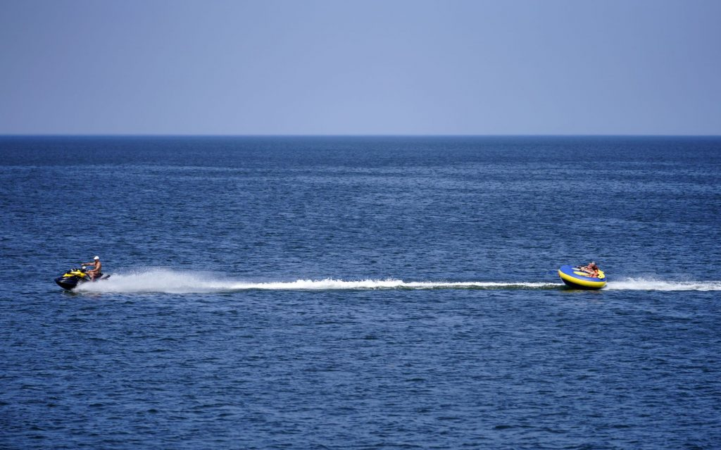 A tube being towed across the water from a jet ski
