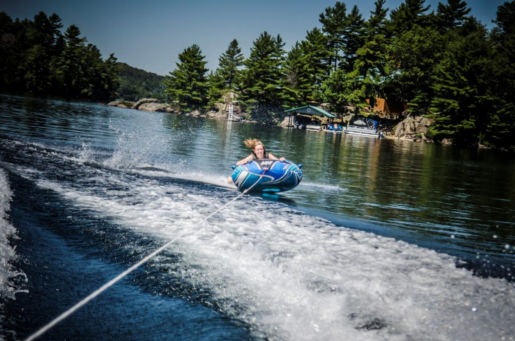 A woman on a tube being pulled across a lake by a speedboat
