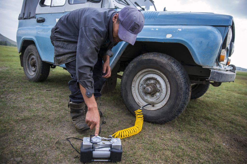 A man turns on a battery-powered air compressor whose hose is attached to his SUV's right front tire