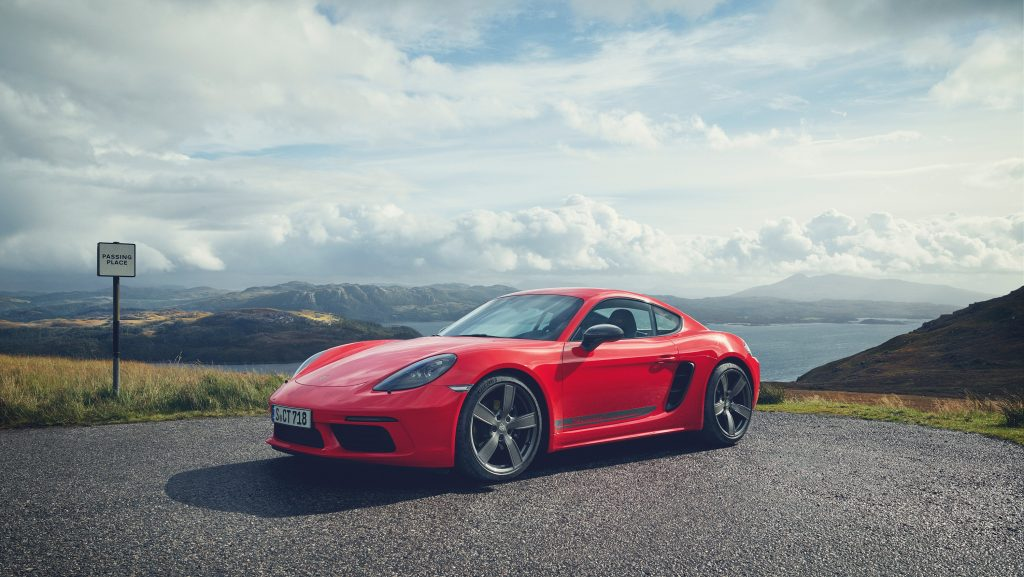 A red 718 Cayman overlooking a bay