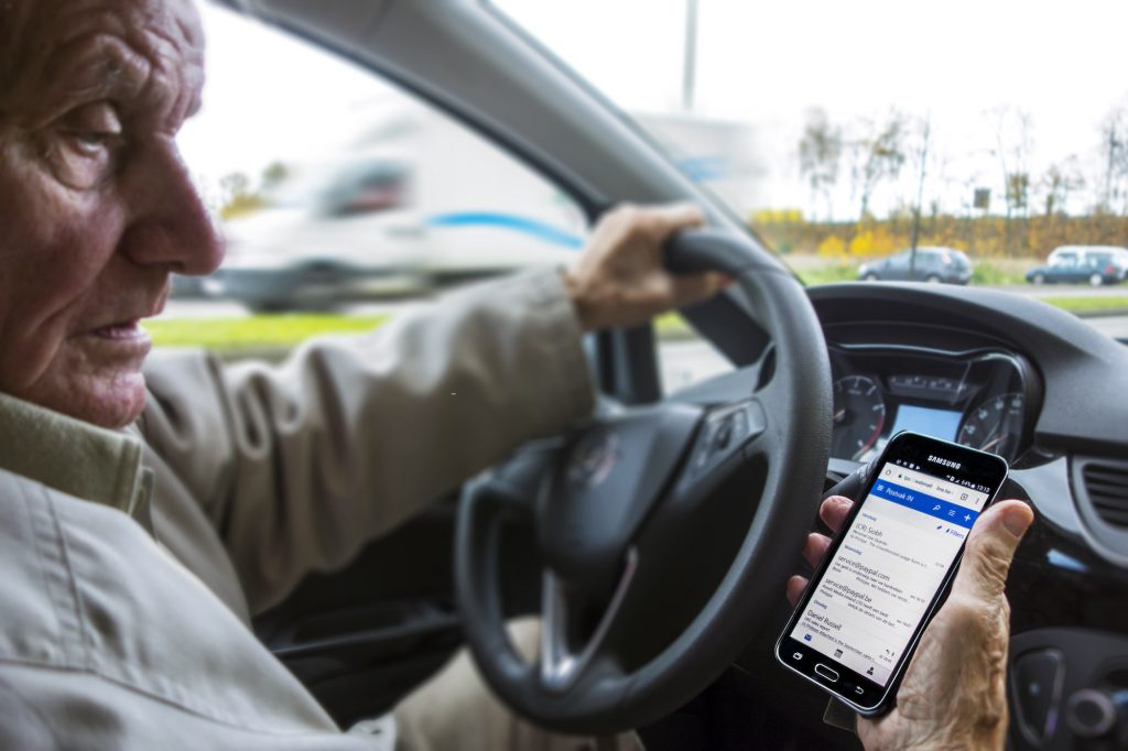 Scary driving habits including checking your phone messages while driving, like this man sitting behind the wheel of a car