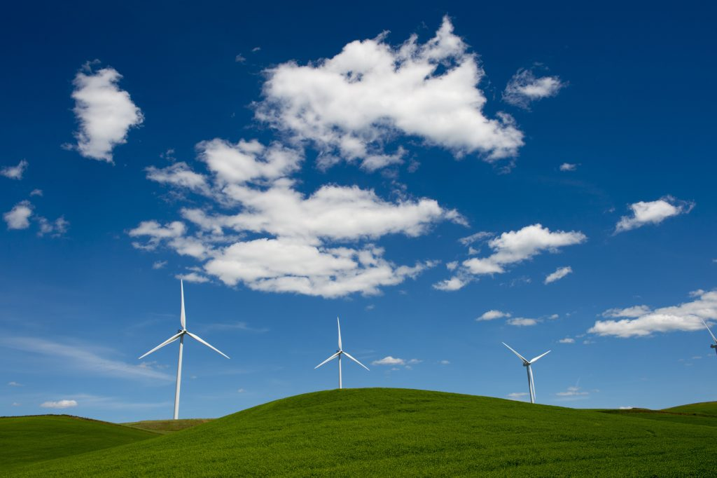 A clear blue sky with white clouds above wind turbines on green grass-covered hills