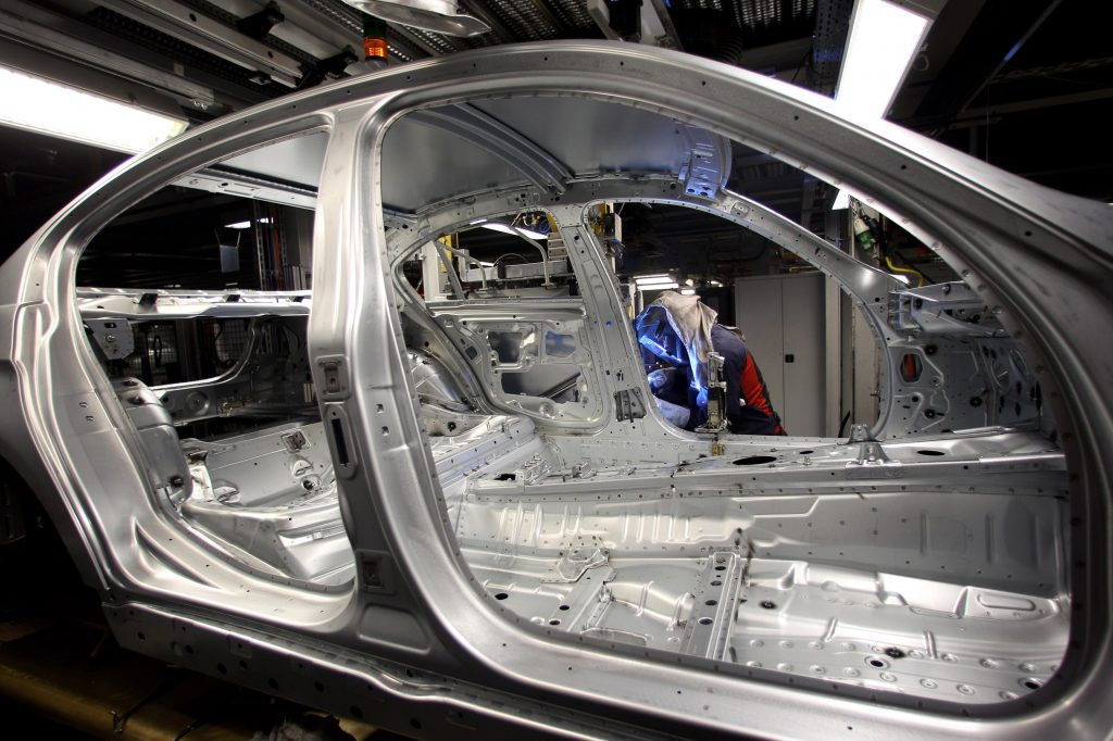 A man attaches a door to the car body on the BMW 3-series production line.