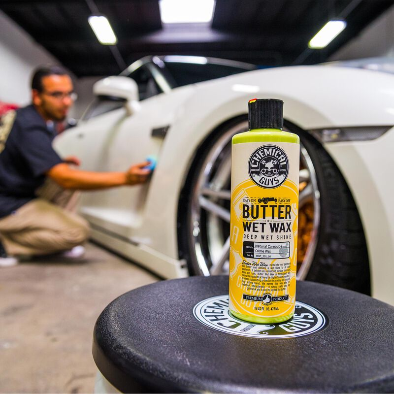 Chemical Guys Butter Wet car wax sits on a stool while a man polishes a white Nissan GTR in the background