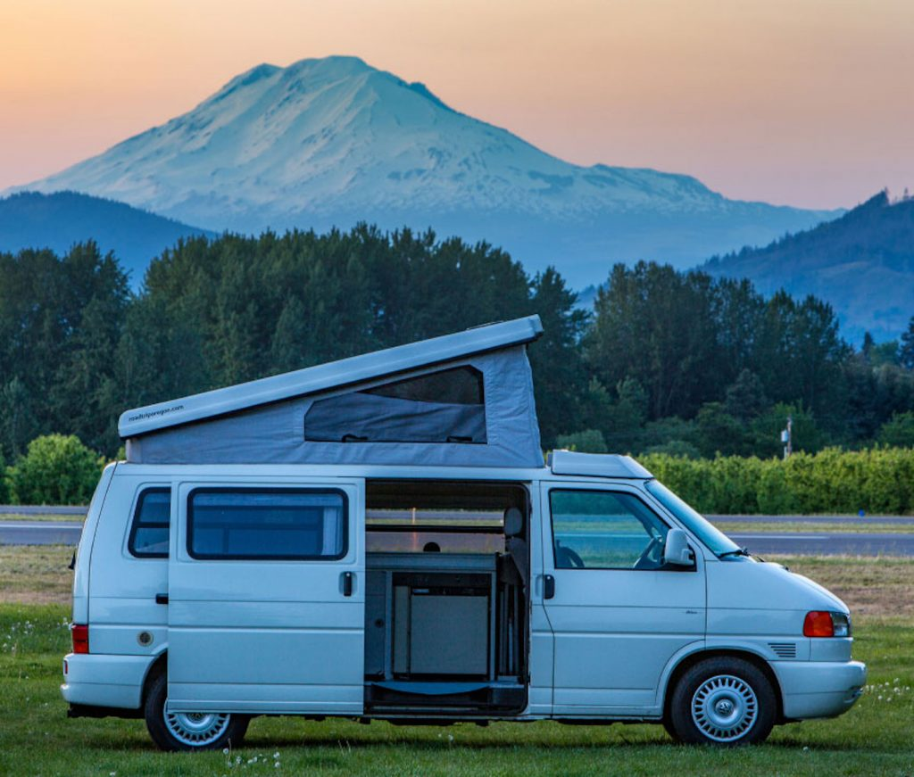 A Volkswagen European parked in a field at dusk with a mountainous backdrop and the pop top open