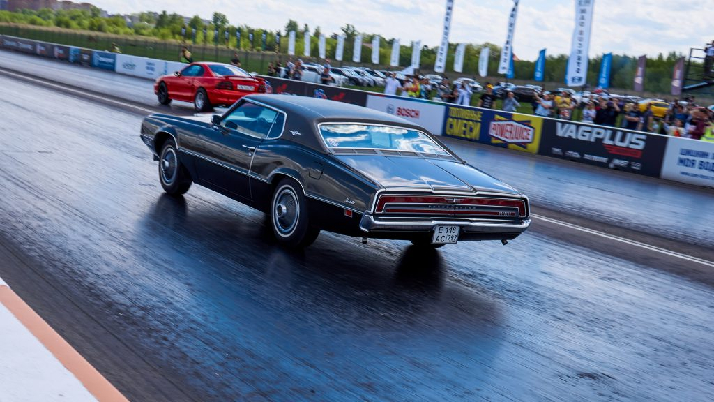 A brown and red muscle car racing during the event.