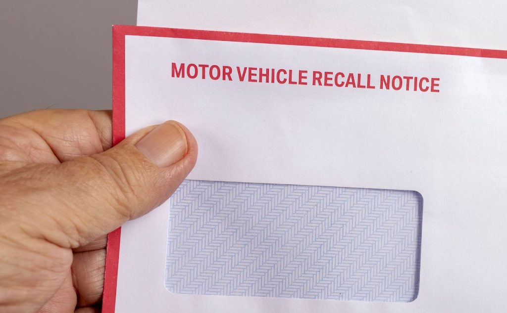 A white envelope with 'motor vehicle recall notice' written in red uppercase font