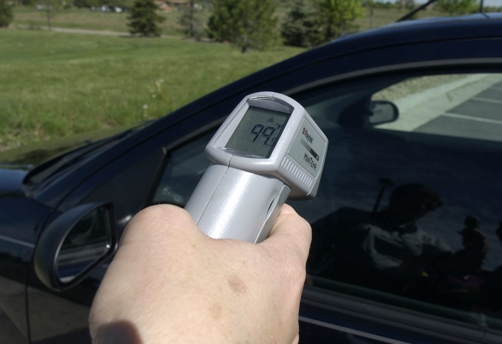 A man takes the interior temperature of a car.