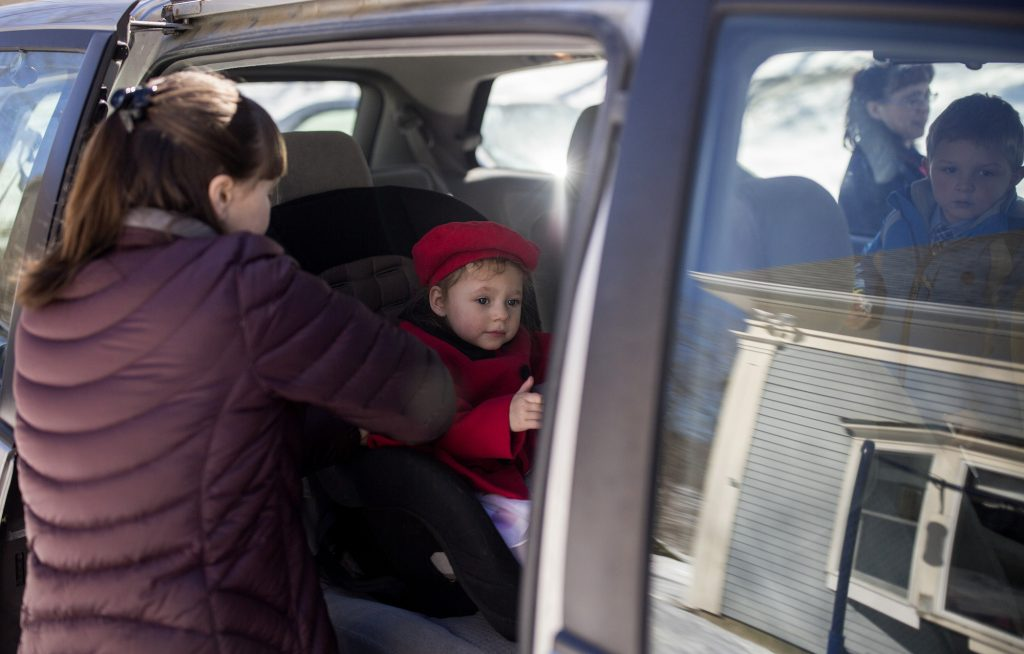 Hannah DeWick, 15, straps her newly adopted sister, Paisley, 2, into her car seat in a minivan in Rockport, Maine