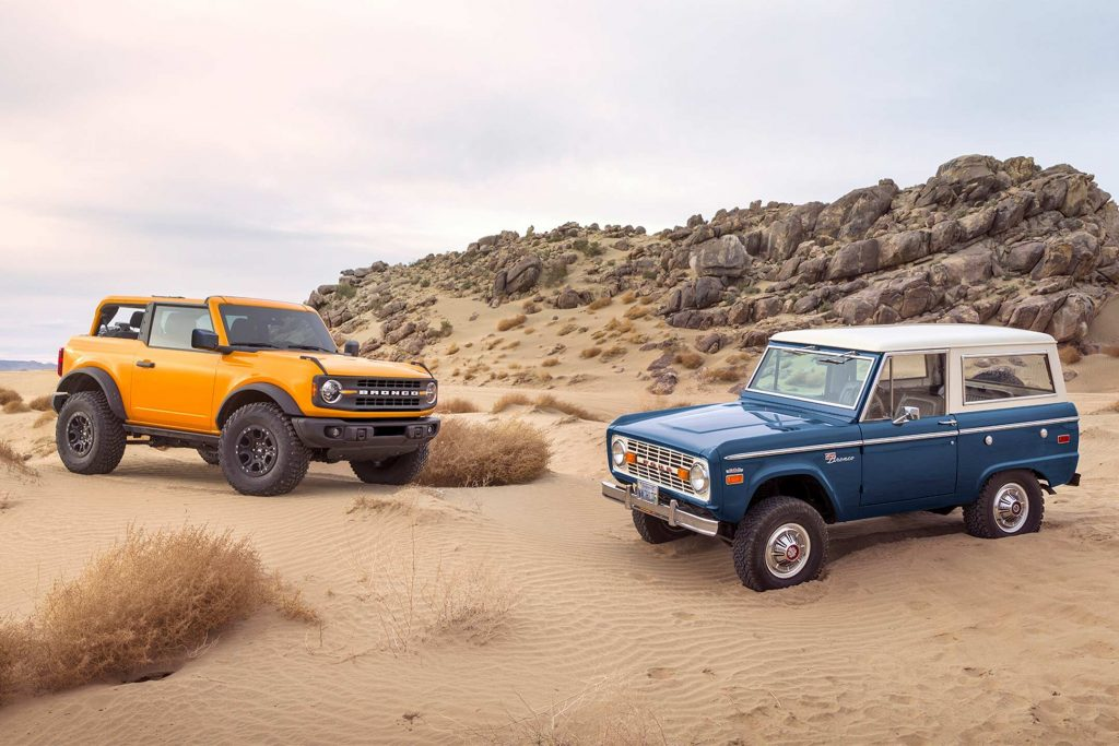 A new Cyber Orange Bronco posed with a classic one on a sand dune