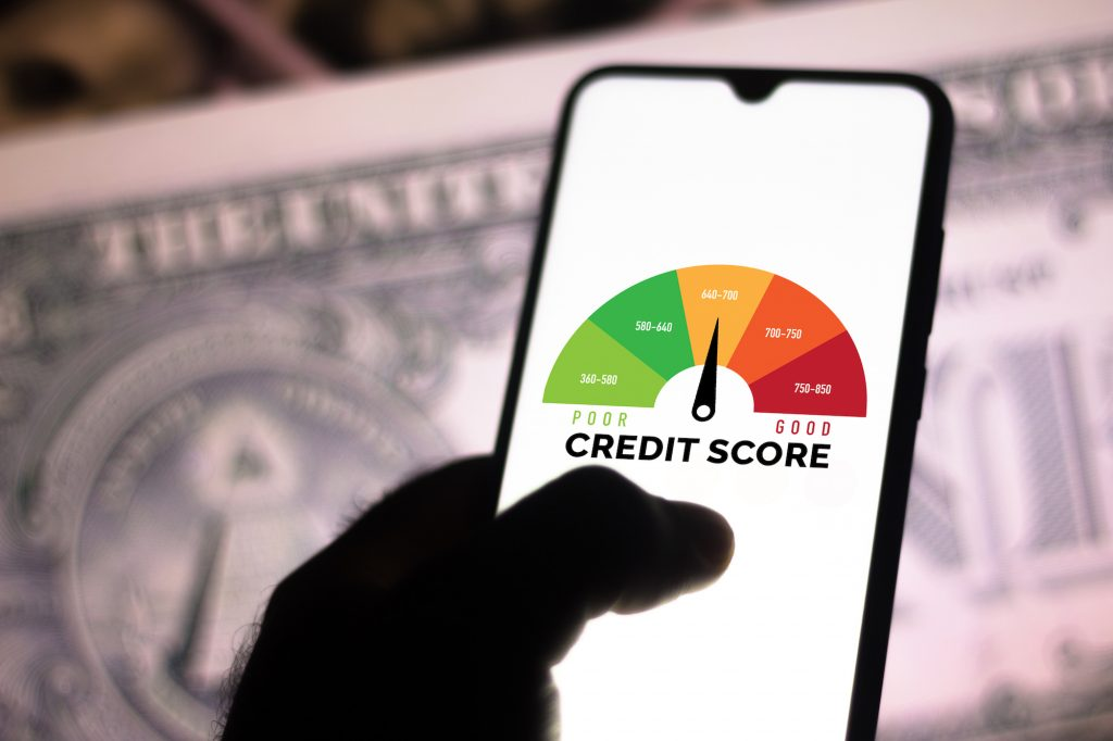 A photo illustration of a hand holding a smartphone showing a graph with the credit score