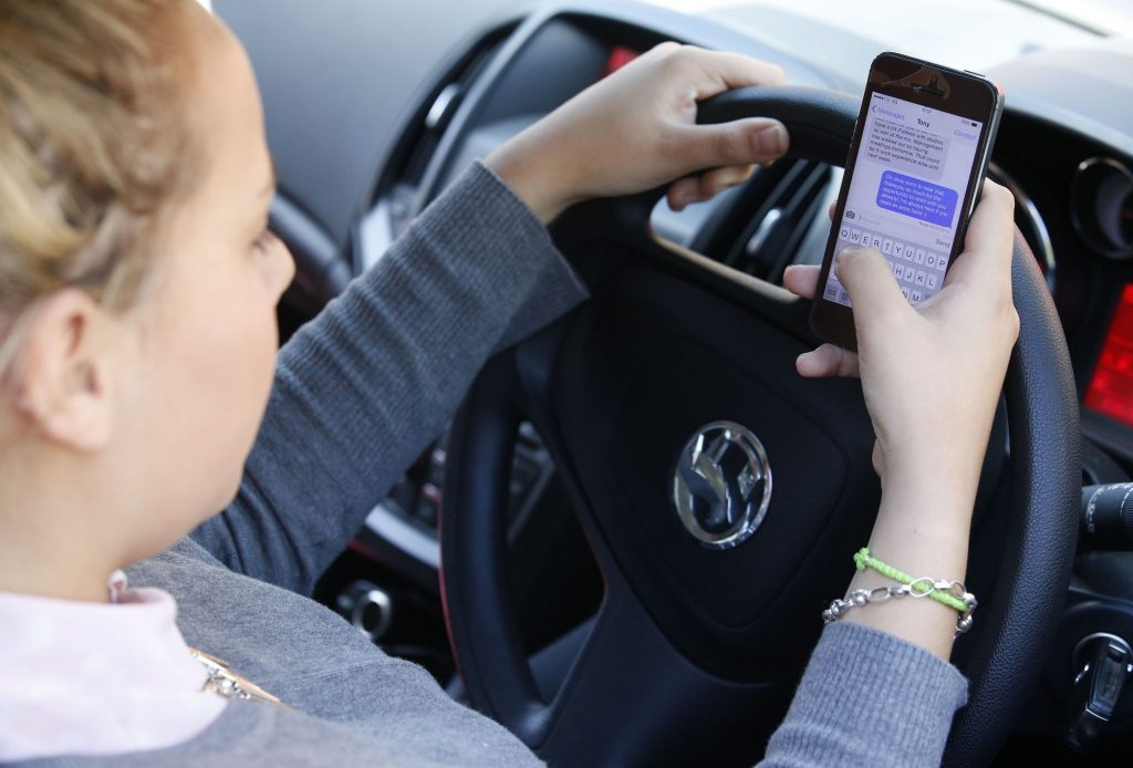 A young woman texts on her phone while driving, the biggest driving distraction