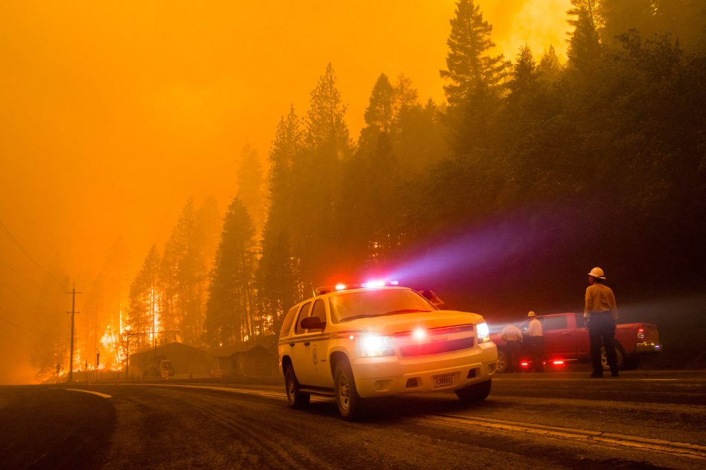 Firefighters block the road as a forest fire reaches a highway in California
